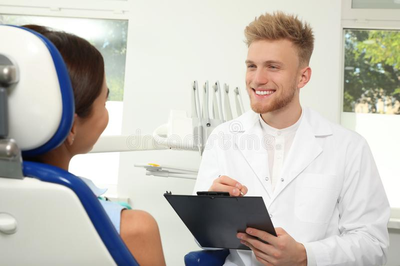 Professional dentist working with patient. In clinic stock image