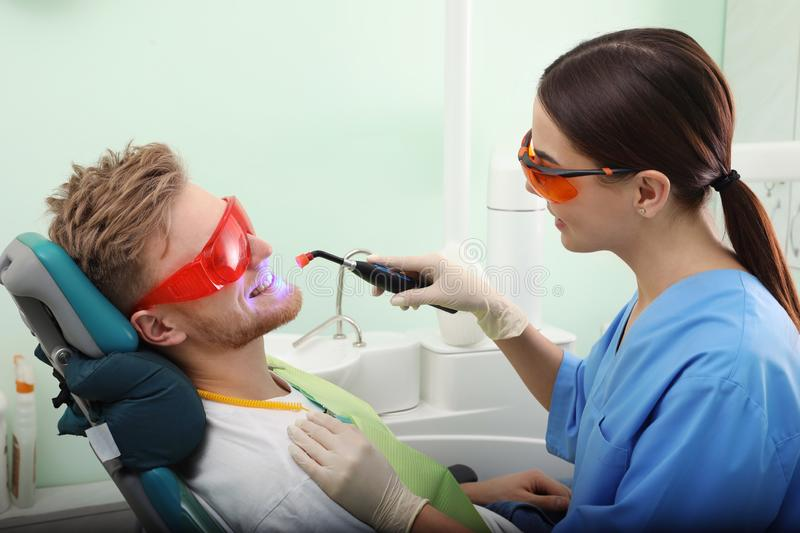Professional dentist working with patient in modern clinic. Teeth whitening stock images