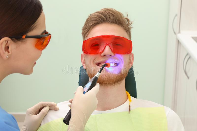 Professional dentist working with patient in modern clinic. Teeth whitening stock image