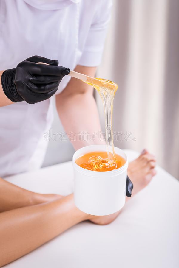 Professional depilation master removing unwanted hair from legs. Unwanted hair. Professional depilation master wearing black gloves removing unwanted hair from stock photo