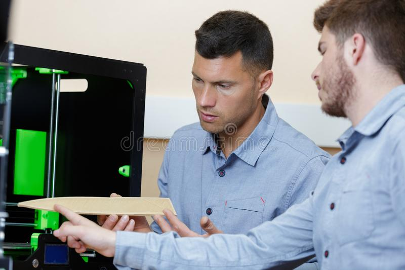 Professional designer and student standing next to 3d printer royalty free stock photo