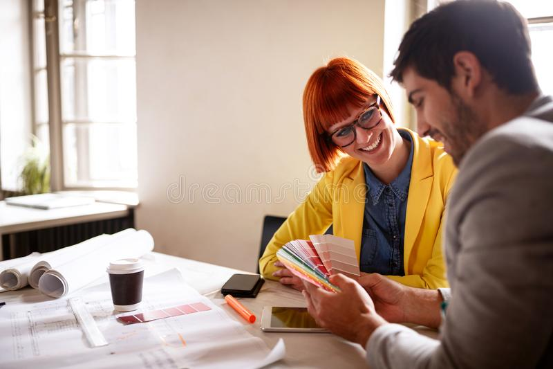 Professional designers looking at color swatches. In hands royalty free stock photography