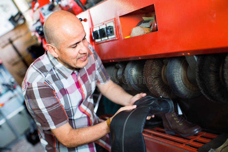 Professional diligent craftsman polishing footwear. On machine in shoe atelier stock images