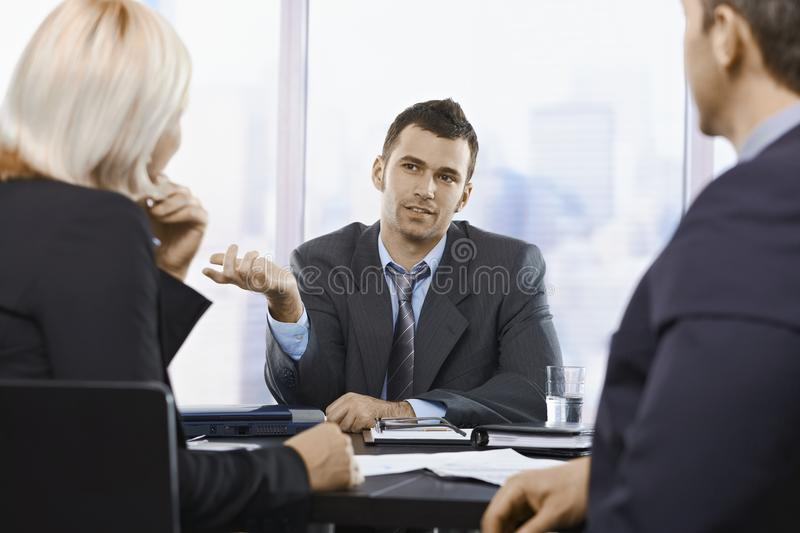Professional discussion. Busy professionals discussing work in office royalty free stock images