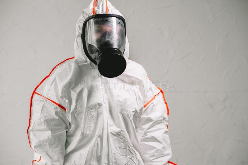 Disinfector wearing protective biological suit and gas-mask conduct disinfection. Professional disinfector wearing protective biological suit and gas-mask royalty free stock photo