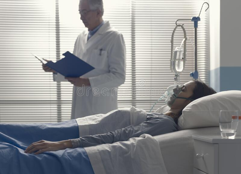 Professional doctor assisting a patient and checking medical records royalty free stock photography