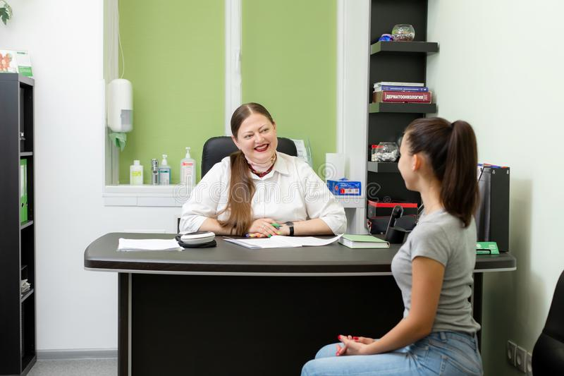 Professional doctor dermatologist advises young woman patient stock image
