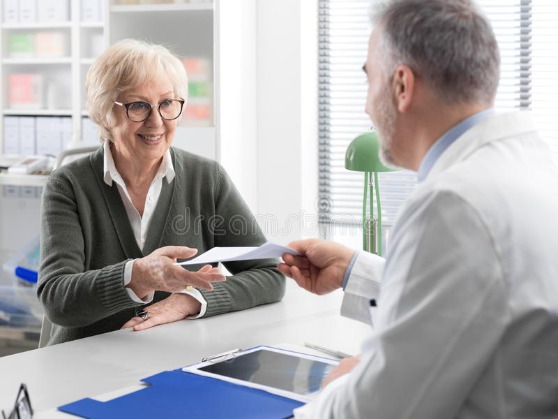 Professional doctor giving a prescription to a senior patient stock photo