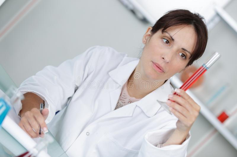 Professional doctor making notes on blood sample. Professional doctor is making notes on blood sample stock photography