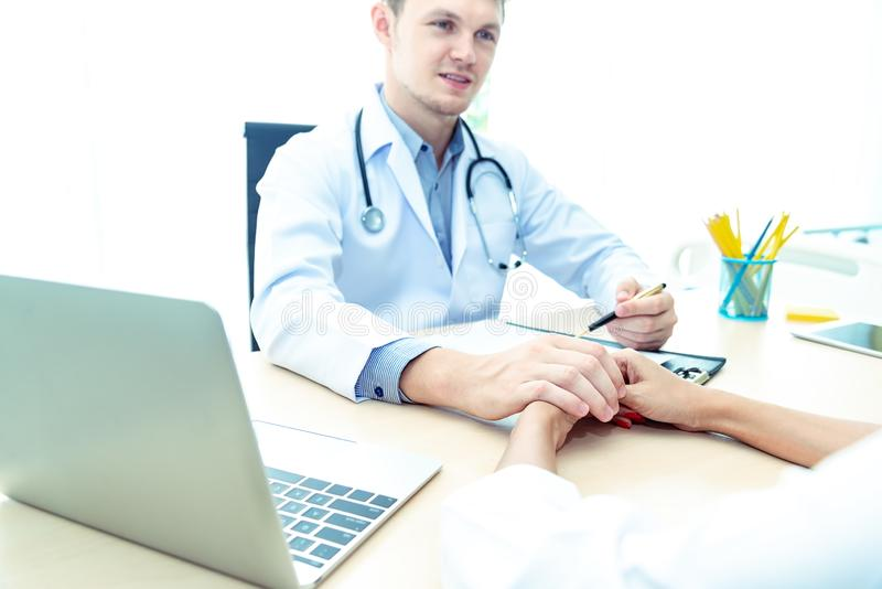 Professional doctor man with stethoscope reassuring woman patient on workplace in hospital.Professional medical doctor comforting. Professional doctor men with stock image