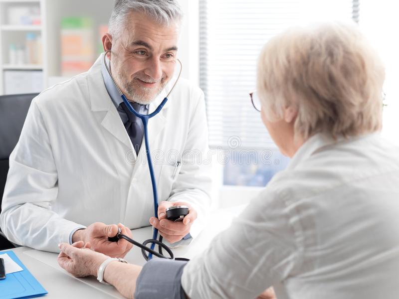 Professional doctor measuring a patient`s blood pressure stock photo