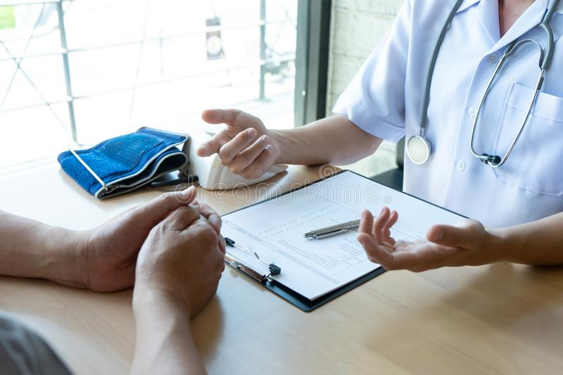 Professional doctor sit at the table and talk to the patient. Professional doctor sit at the table and talk about health care to the patient, on the table there stock photography