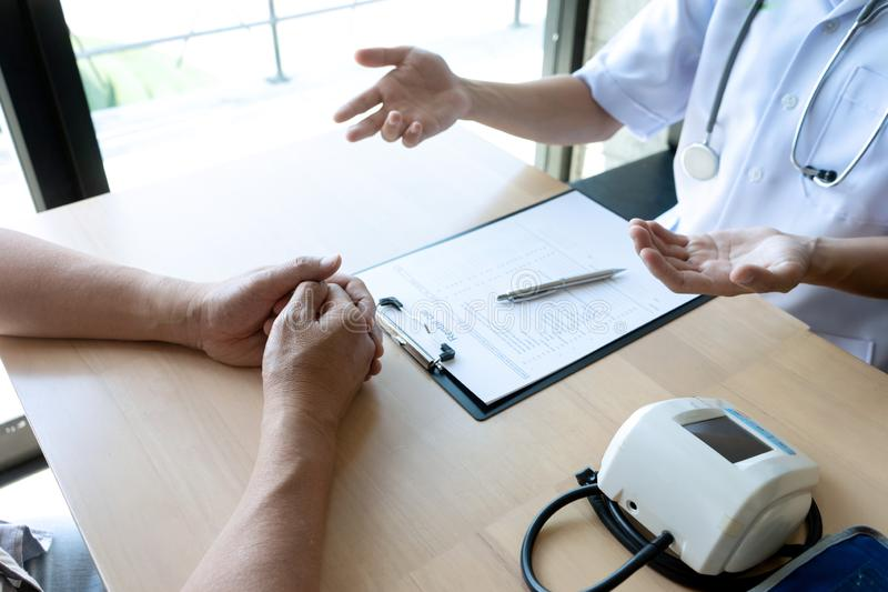 Professional doctor sit at the table and talk to the patient. Professional doctor sit at the table and talk about health care to the patient, on the table there stock photos