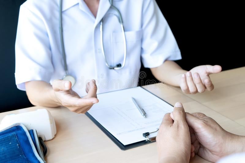 Professional doctor sit at the table and talk to the patient. Professional doctor sit at the table and talk about health care to the patient, on the table there stock image
