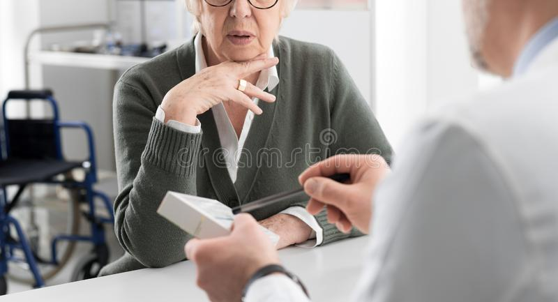 Professional doctor giving a prescription medicine to a senior patient royalty free stock photography