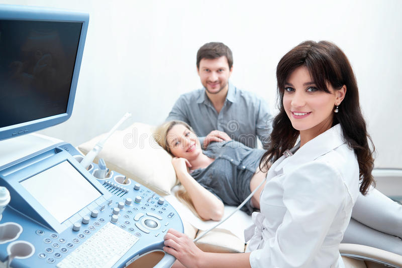 Professional doctor using ultrasound equipment screening pregnant woman. royalty free stock photos