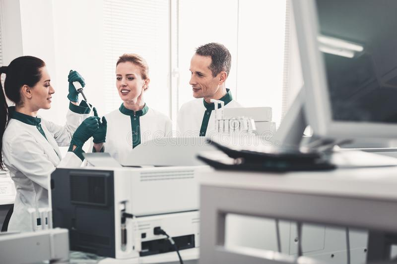 Professional doctors teaching their assistant. First experience. Professional positive doctors being pleased while teaching their new assistant and expressing stock image