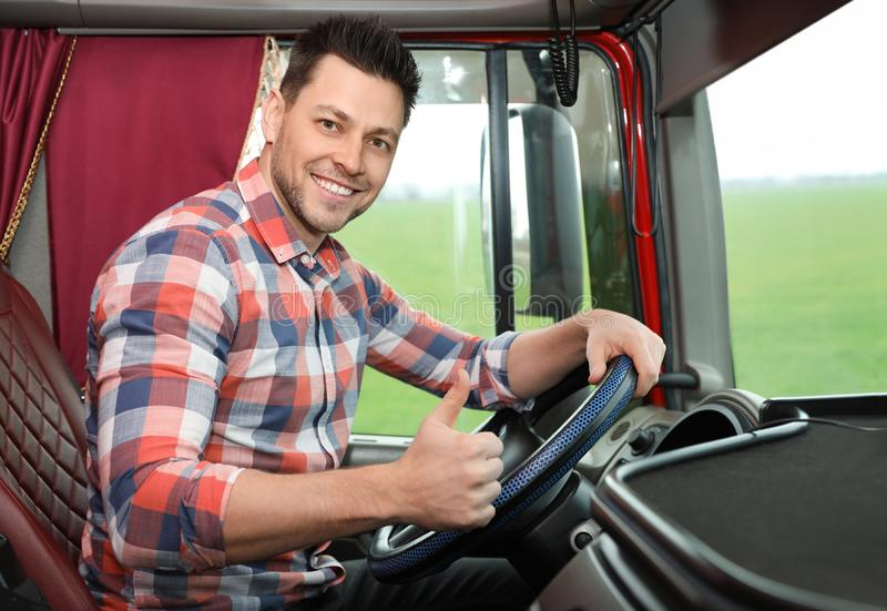 Professional driver sitting in cab of truck stock photography