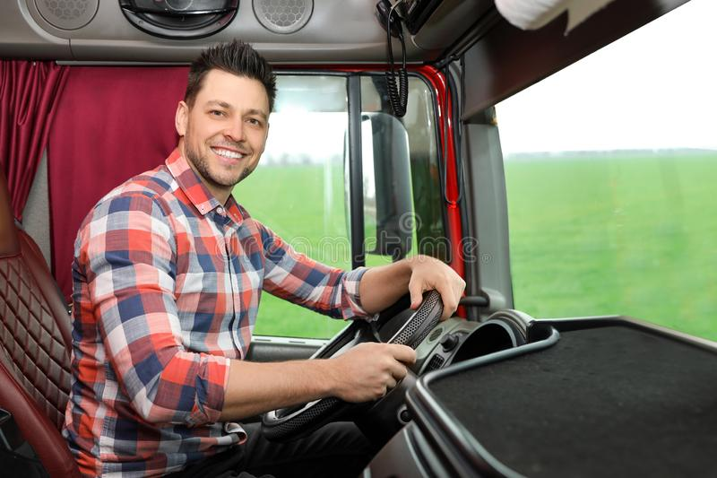 Professional driver sitting in cab of truck. Professional driver sitting in cab of modern truck stock image