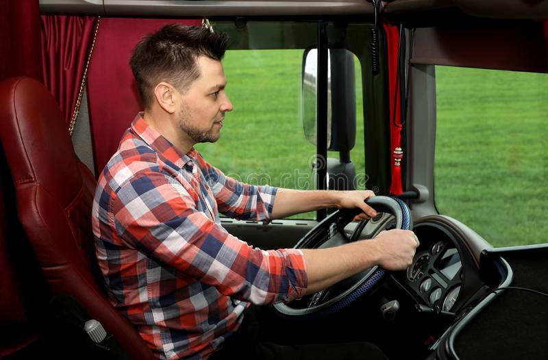 Professional driver sitting in cab of truck. Professional driver sitting in cab of modern truck royalty free stock photo