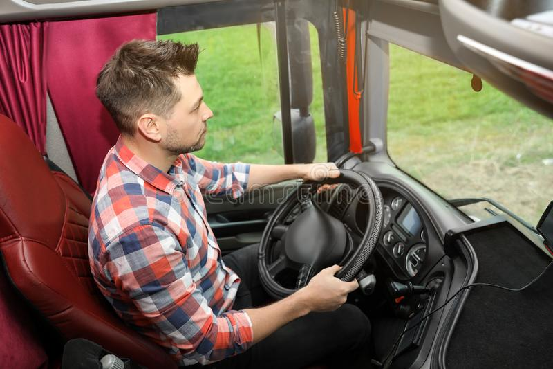 Professional driver sitting in cab of truck stock photos