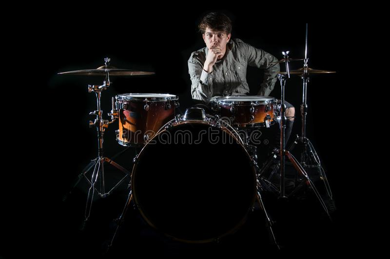 Professional drummer playing on drum set on stage on the black background stock photo