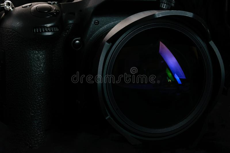 Professional DSLR camera background. Photography occupation background image concept - professional modern DSLR camera with wide lens in close-up low key light royalty free stock photos