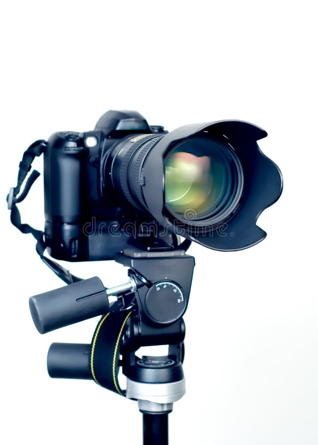 Professional DSLR camera with telephoto zoom lens on tripod royalty free stock images