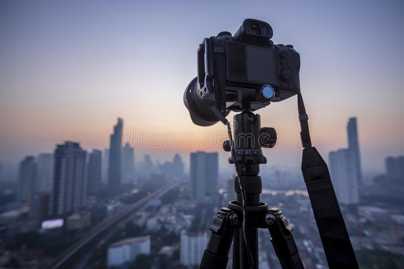 Professional DSLR Mirrorless camera on a tripod,  taking pictures of the beautiful moments during the sunset ,sunrise stock photography