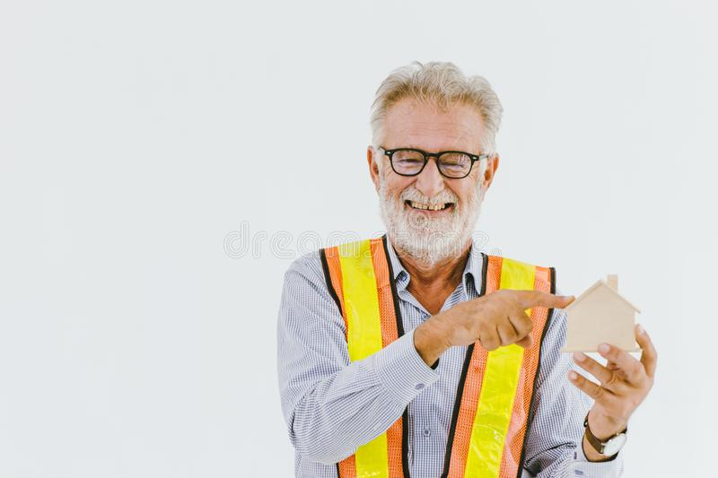 Professional elder home engineer builder hand pointing at house model happy and smiling with space for text stock photo