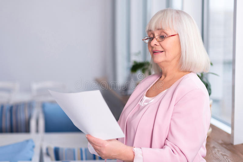 Professional elderly woman reading a document stock image