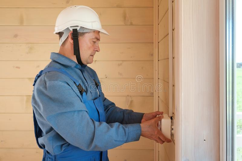 professional electrical engineer performs installation of electrical sockets royalty free stock image