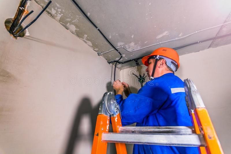 Professional electrician installs wiring stock images