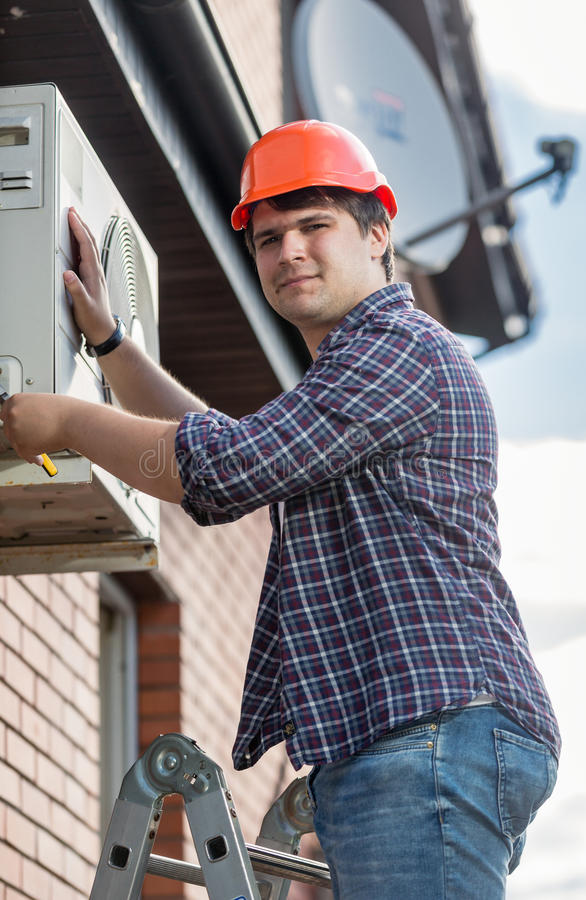 Professional electrician repairing air conditioner on outer wall stock photography