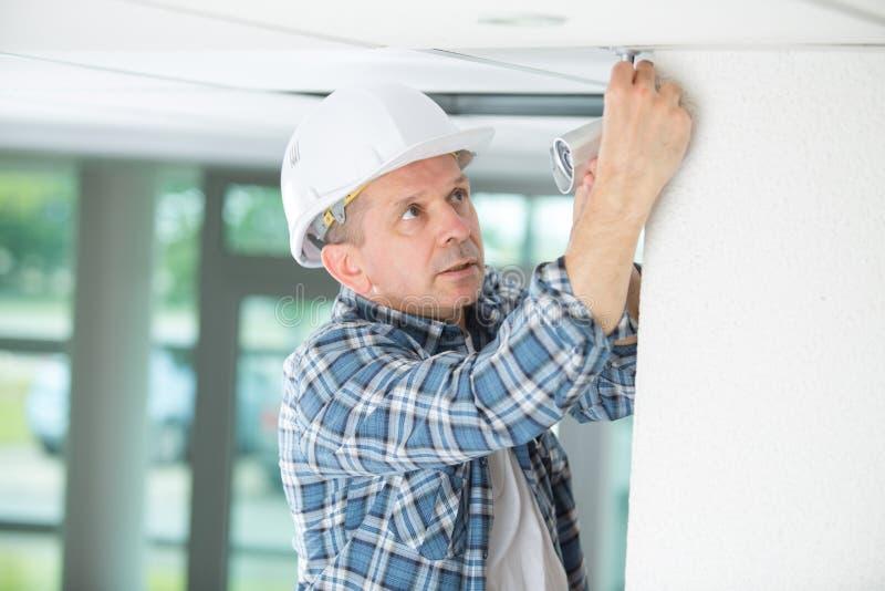 Professional electrician replacing light bulb at home stock photos