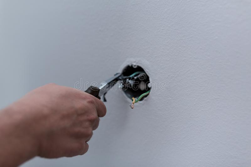 Electrician stripping the cable to connect switches and sockets stock photos