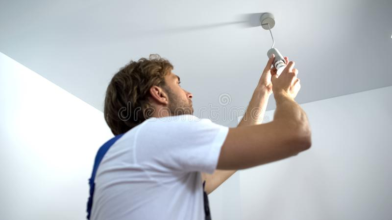 Professional electrician twisting bulb installing light in apartment, service. Stock photo royalty free stock photo