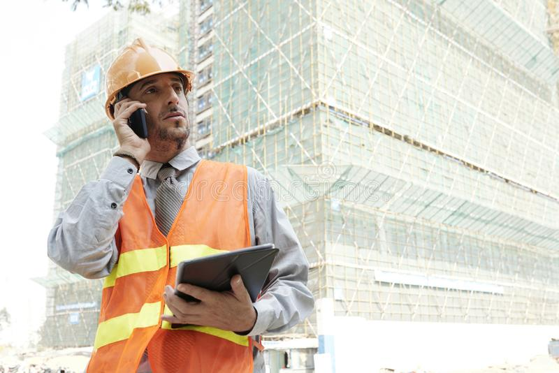 Engineer calling coworker. Professional engineer in hard hat standing at constructing site and calling coworker stock image