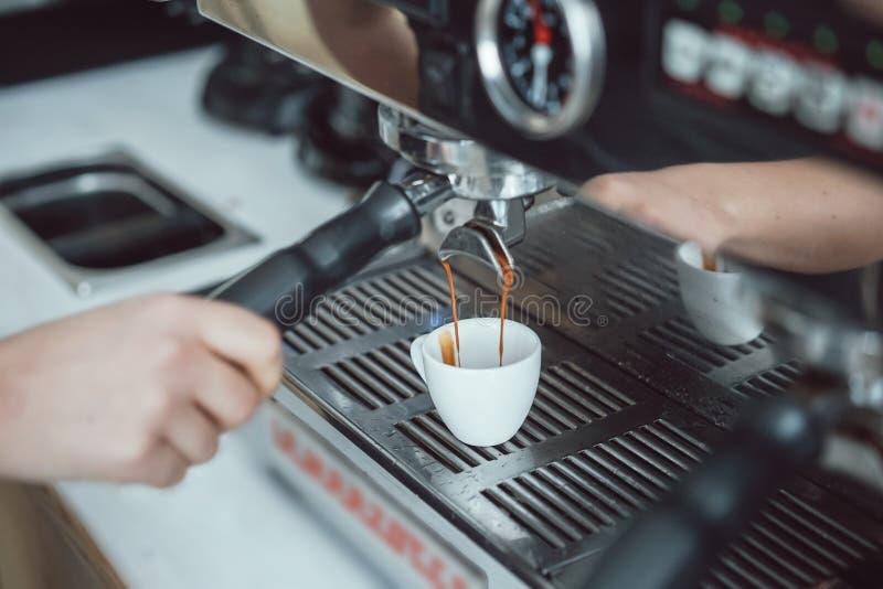 Professional espresso machine pouring fresh coffee into white ceramic cup stock photography