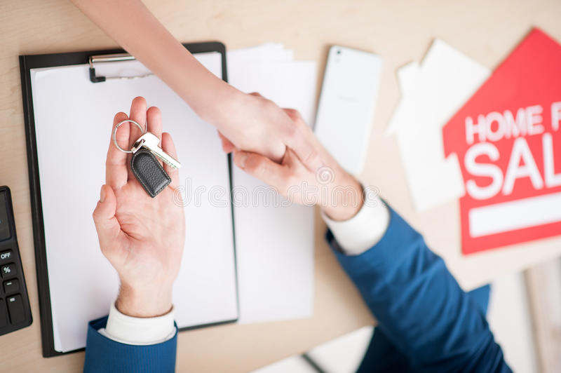 Professional estate agent is selling a house. Close up of arms of realtor and customer shaking hands. They are sitting at the desk. The men is giving a key to stock photos