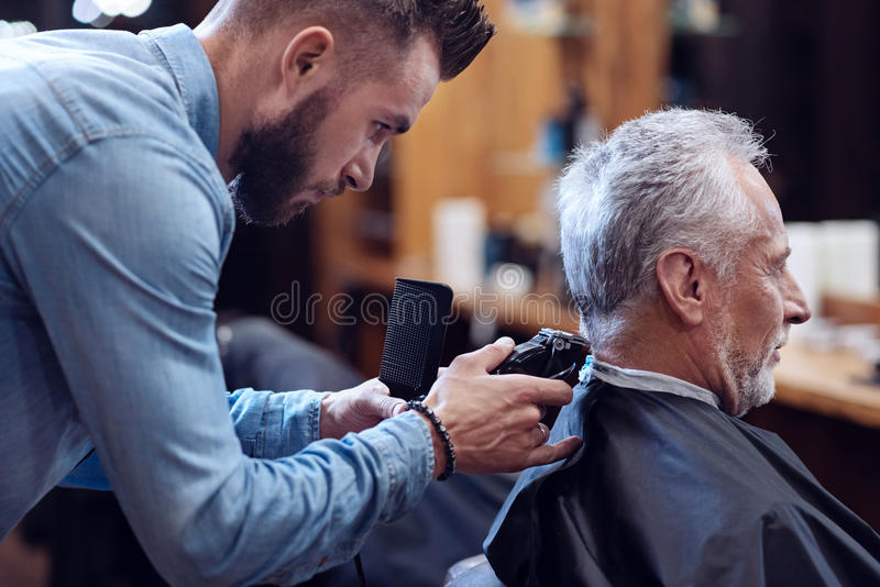 Professional experienced barber working with hair cutting machine. Modern hairstyle. Professional experienced bearded barber holding a comb and using a hair stock images