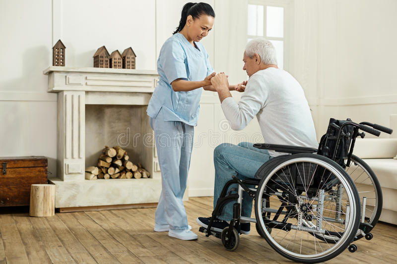 Professional experienced caregiver looking after her patient. Be careful. Professional experienced female caregiver holding her patients hands and helping him to royalty free stock images