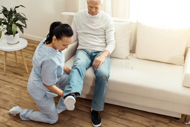 Professional experienced caregiver warming up her patients leg. Special exercise. Pleasant professional experienced caregiver sitting on one knee and warming up royalty free stock photography