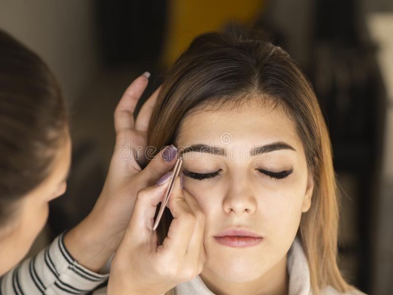 Professional eyebrow shape correction procedure. Beautician plucking eyebrows with tweezers close up royalty free stock photo
