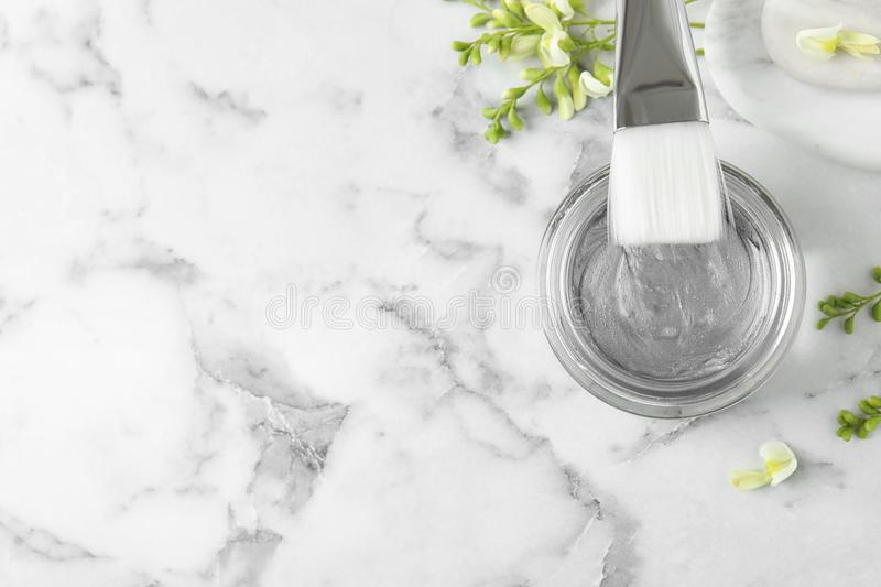 Professional face  with brush and flowers on white marble table, flat lay. Space for text. Professional face mask with brush and flowers on white marble table stock photos