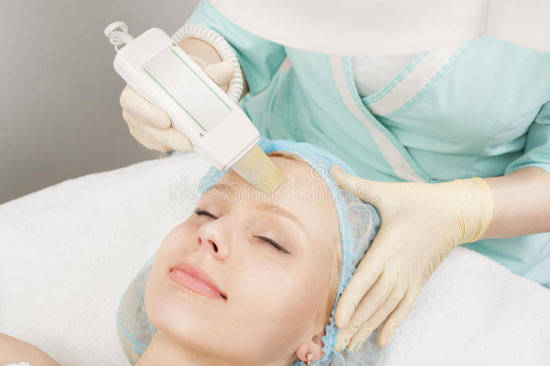 Professional face cleaning. Young women having Beauty treatment receiving therapy with ultrawave skin care instrument stock photos