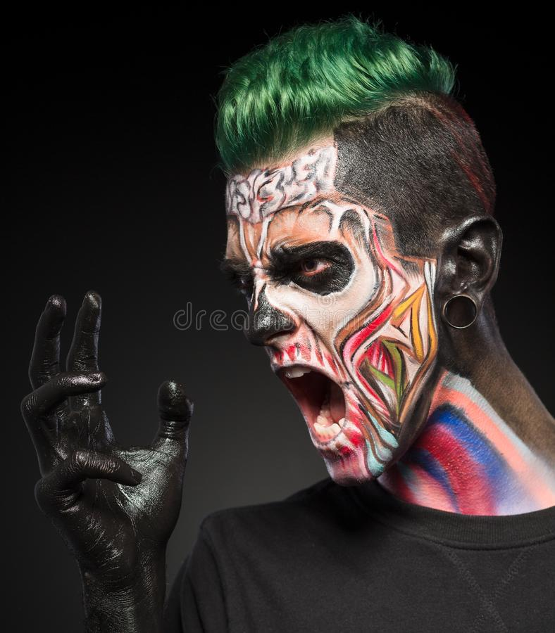 Professional fashion skull makeup. Fantasy art makeup on mans face isolated on black background stock images
