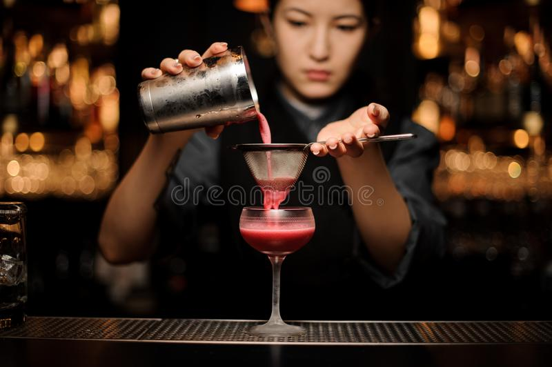 Professional female bartender pouring a smooth crimson cocktail through the sieve to the glass stock photography