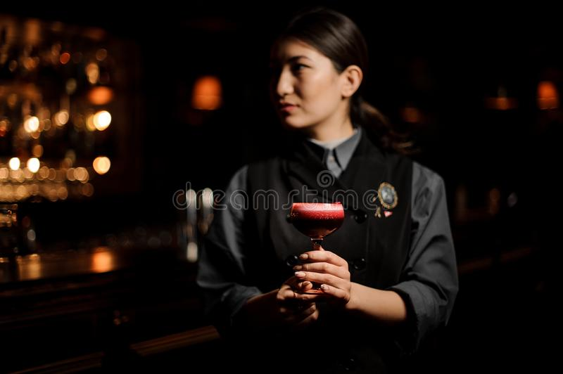 Professional female bartender serving a smooth crimson cocktail in the glass with a one pink rose bud as a decor stock image