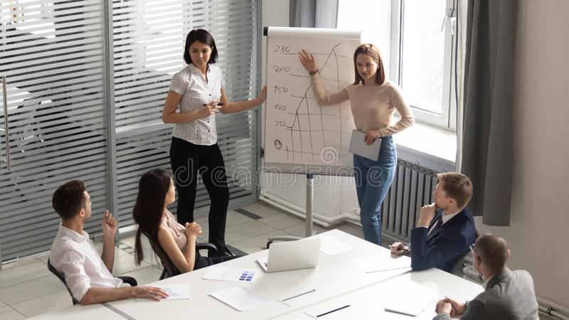 Professional female business trainers giving flip chart presentation to employees. royalty free stock photo